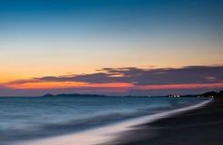 在海海滩的软的波浪在天空蔚蓝和橙色云彩太阳落山 库存照片
