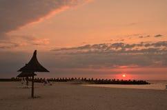在海海滩,芦苇伞,风景的日出 免版税库存照片