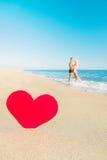 在海海滩和大红色心脏-圣情人节conce的夫妇 图库摄影