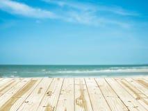 在海海滩模糊的背景的木台式 库存图片