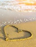 在海海滩沙子画的心脏,软的波浪在一个晴天 自然 免版税库存图片
