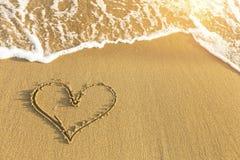 在海海滩沙子画的心脏,软的波浪在一个晴朗的夏日 爱 免版税库存照片