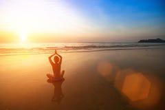 在海海滩的女子实践的瑜伽在美妙的日落期间 免版税库存照片