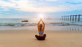 在海海滩的女子瑜伽 库存照片