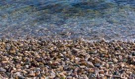 在海海滩的色的小卵石 背景有启发性岩石向星期日扔石头 免版税图库摄影