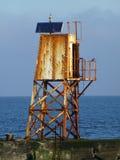 在海港入口的生锈的老灯塔烽火台 免版税库存照片