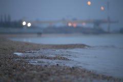 在海港附近的夜海滩 图库摄影