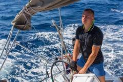 在海游艇况赛期间,一个人控制一条帆船小船 体育运动 库存图片