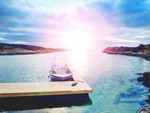 在海湾口岸,日落镇静水的渔船 体育运动垂钓的一艘汽艇 免版税库存图片