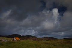 在海湾旁边的小的石小屋 库存图片