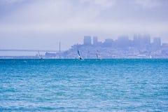 在海湾的小船在背景中浇灌,雾部分地报道的旧金山地平线 免版税库存图片
