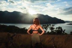 在海湾的少妇赞赏的日落 免版税库存照片