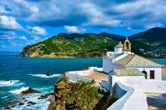 在海湾的白色教会在一多云天,斯科派洛斯岛,希腊 库存照片