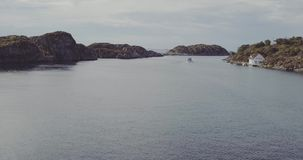 在海湾的飞行有反对岩石银行的小船的有房子的 影视素材