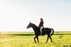 在海湾马的年轻有吸引力的女孩骑马 免版税库存照片