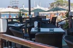在海滨的旅游咖啡馆有在小船在口岸和棕榈的一个看法沿海,海,土耳其 库存照片