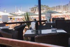 在海滨的旅游咖啡馆有在小船在口岸和棕榈的一个看法沿海,海,土耳其 免版税图库摄影