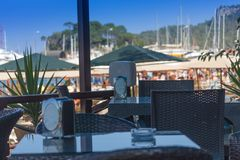 在海滨的旅游咖啡馆有在小船在口岸和棕榈的一个看法沿海,海,土耳其 免版税库存照片
