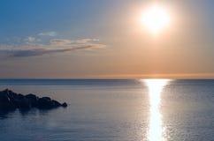 在海滨的石壁架 日出 海天线,反射 库存照片