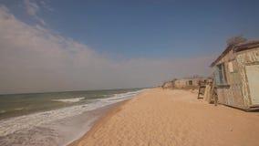 在海滨,秋天心情在海边,滚动沿海滩的波浪的被毁坏的大厦 影视素材