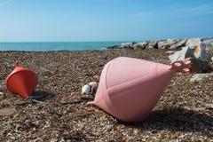 在海滩、天蓝色的海和多岩石的海滩的两个大浮体 库存照片