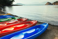在海滩、海和山的五颜六色的独木舟小船在后面 免版税图库摄影