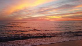 在海滩与美妙的淡色色的天空和波浪的令人敬畏的金黄小时日落在岸碰撞了 股票录像