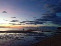 在海滩人走的日落 库存照片