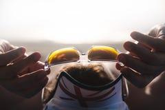 在海滩佩带的太阳镜的旅客sunbaths和用手拿着他们 太阳镜特写镜头,背景被弄脏 免版税库存图片