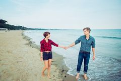 在海滩假期爱走在海岸的夫妇握手 恋人愉快的片刻的概念在度假 男朋友和girlfr 免版税库存照片