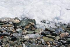 在海滩关闭的湿小卵石石头 免版税库存照片