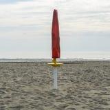 在海滩关闭的红色伞 免版税库存图片