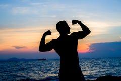 在海滩剪影的肌肉在日落 免版税库存照片