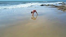 在海滩和女孩的泡沫似的波浪卷瑜伽姿势特写镜头的 股票录像