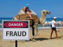 在海滩和骆驼乘坐的孩子的标志危险scammers 库存照片