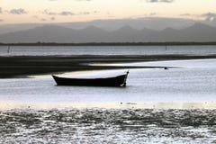 在海滩和montains的一条小船 库存照片