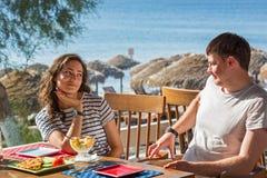 在海滩咖啡馆的年轻夫妇 免版税库存照片