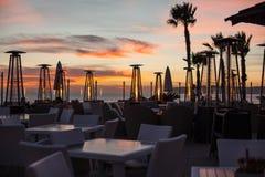在海滩咖啡馆的美好的浪漫日落与室外露台加热器 库存图片