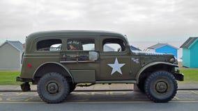 在海滩小屋前面的沿海岸区散步停放的葡萄酒美国军车 免版税库存图片
