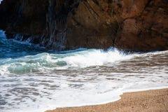 在海滩岩石附近的海浪 库存照片