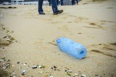 在海滩投下的肮脏的塑料瓶 库存图片