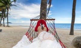 在海滩摇篮的妇女 免版税库存照片