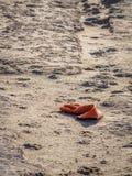 在海滩放弃的橙色手套在日落 库存照片