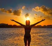 在海滩日落开放胳膊的女孩剪影 免版税图库摄影