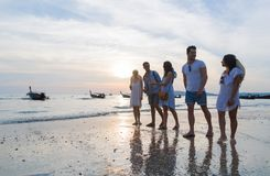 在海滩日落暑假,朋友走的海边的青年人小组 免版税库存照片