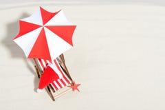 在海滩概念的圣诞快乐 与伞和圣诞老人帽子的躺椅 免版税库存图片