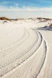 在海滩沙丘的轮胎轨道在黄昏 库存照片