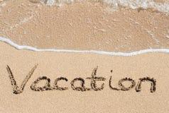 在海滩沙子写的假期  库存图片