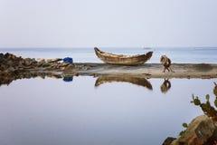 在海滩沙子反射停住的偏僻的木渔船在死水 免版税图库摄影