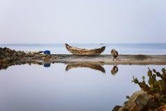 在海滩沙子反射停住的偏僻的木渔船在死水 库存图片